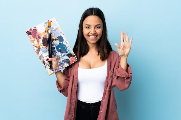 幸せな表情で手で敬礼青い壁にパレットを置く若いアーティストの女性。