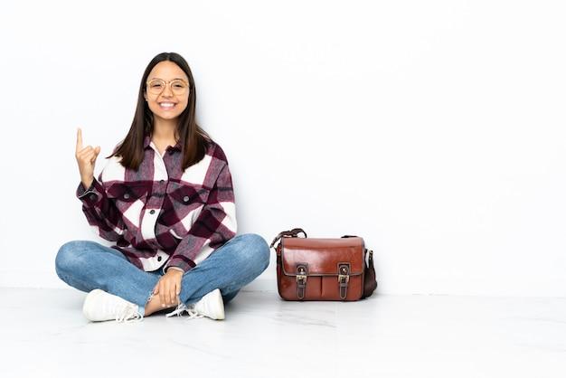 素晴らしいアイデアを指している床に座っている若い学生女性