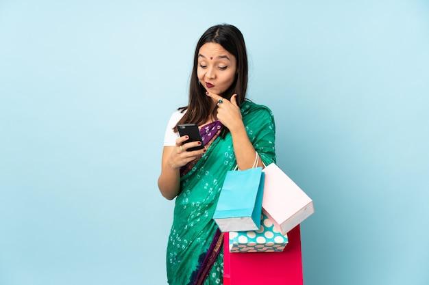 思考とメッセージを送信する買い物袋を持つ若いインド人女性