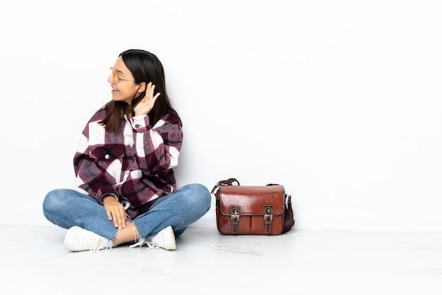 Молодой студент женщина сидит на полу, слушая что-то, положив руку на ухо