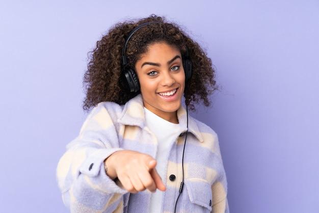 Молодая афроамериканская женщина на фиолетовой стене слушая музыку