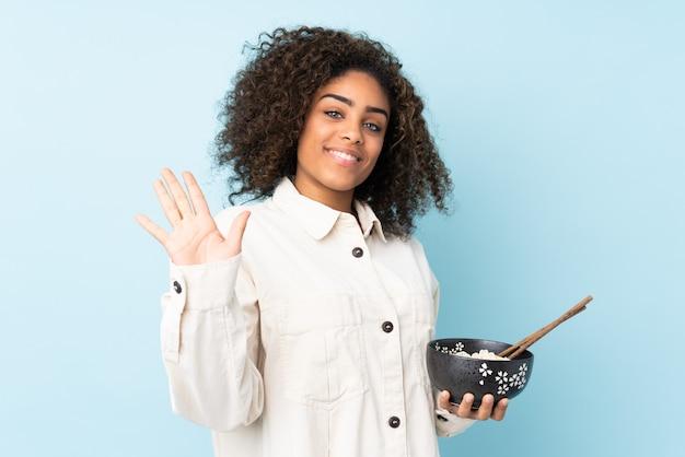 箸で麺のボウルを押しながら幸せな表情で手で敬礼青い壁に若いアフリカ系アメリカ人女性