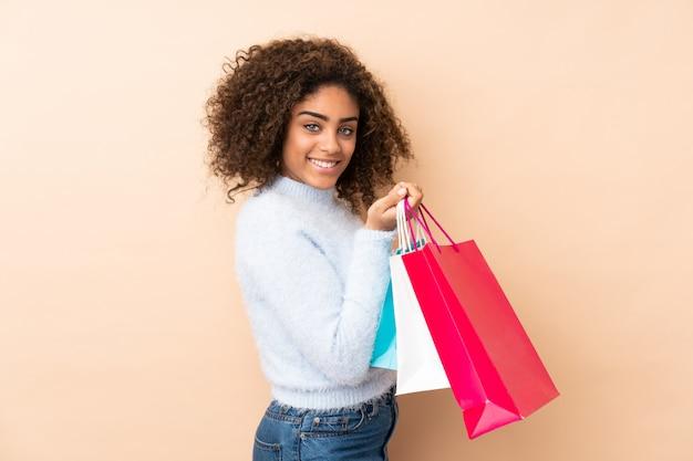 買い物袋を押しながら笑みを浮かべてベージュの壁に若いアフリカ系アメリカ人女性