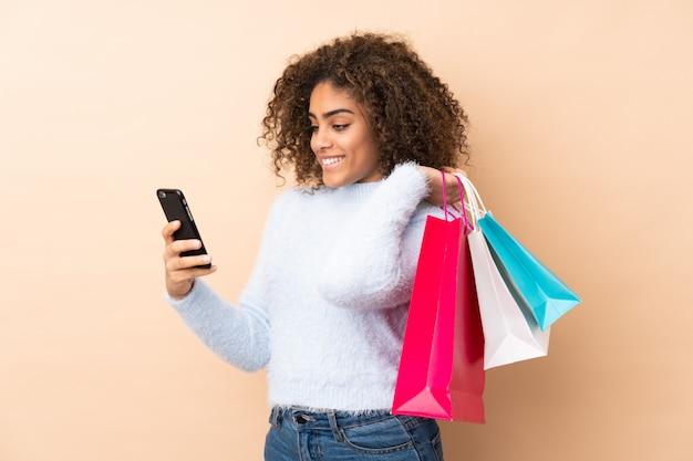 買い物袋を押しながら友人に彼女の携帯電話でメッセージを書くベージュの壁の若いアフリカ系アメリカ人女性