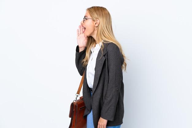 Бизнес уругвайская женщина над белой стеной кричит с широко открытым ртом