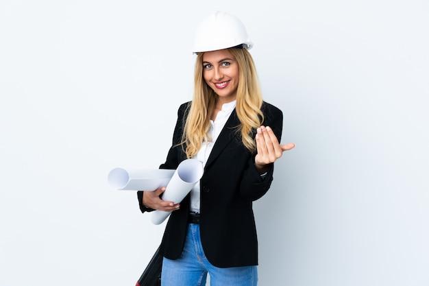 ヘルメットと白い壁に青写真を保持している若い建築家女性