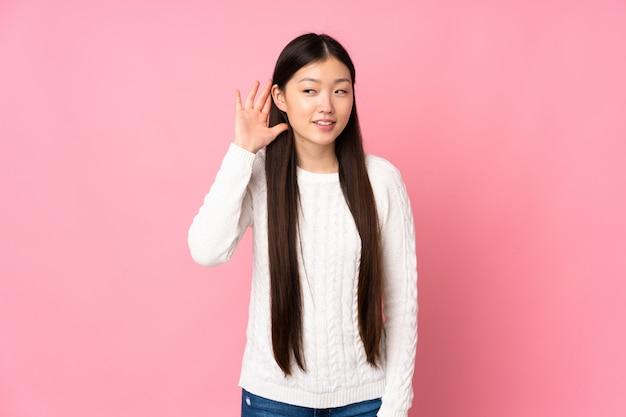 Молодая азиатская женщина над стеной слушая к чему-то, кладя руку на ухо