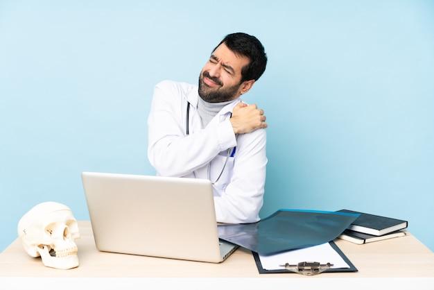 Профессиональный травматолог на рабочем месте, страдающий от боли в плече за усилия