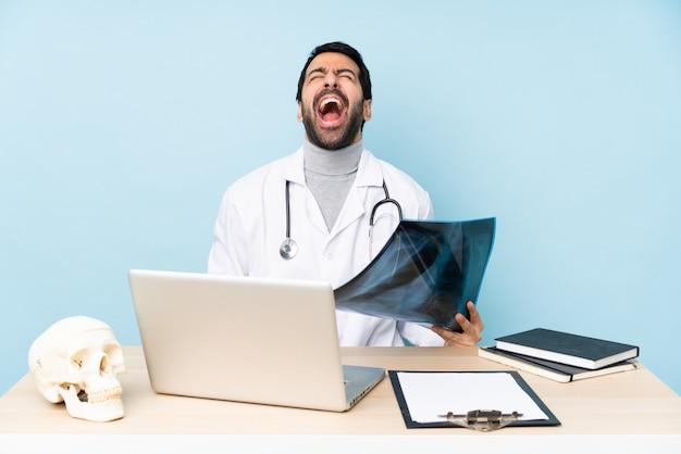 Профессиональный травматолог на рабочем месте кричит вперед с широко открытым ртом