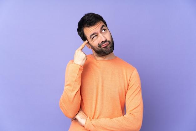 頭に指を置く狂気のジェスチャーを作る紫色の壁を越えて白人のハンサムな男