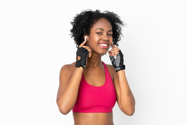 Молодая афро-американская женщина на музыке белой стены слушая