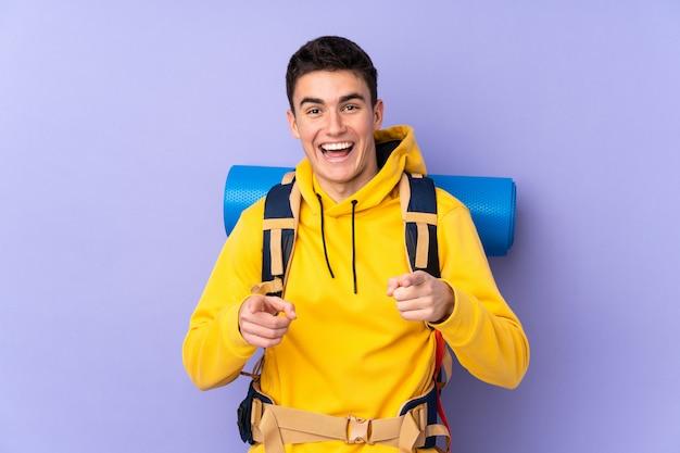 Подросток кавказского альпиниста с большим рюкзаком на фиолетовой стене указывает пальцем на тебя