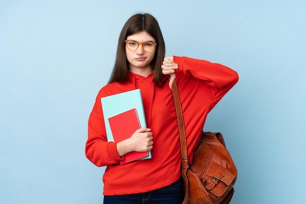 サインを親指を示す青い壁にサラダを置く若いウクライナのティーンエイジャー学生の女の子
