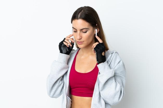 Молодая женщина спорта над музыкой стены слушая