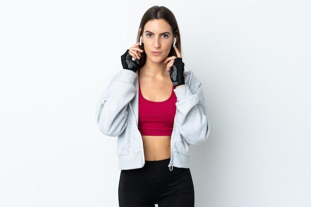 Молодая женщина спорта над музыкой стены слушая и смотря к фронту