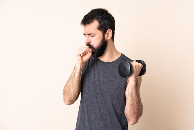 ひげと白人のスポーツ男は多くの咳を壁に重量挙げを作る