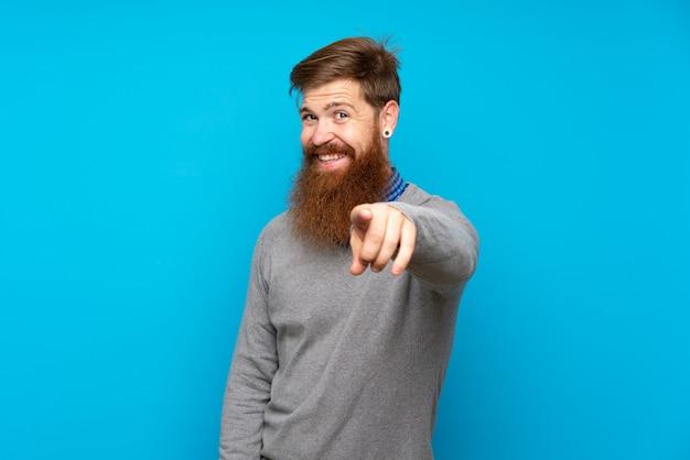 Рыжий мужчина с длинной бородой на синей стене уверенно показывает на тебя пальцем