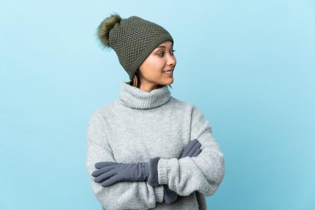 Молодая уругвайская девушка в зимней шапке на синем фоне смотрит в сторону