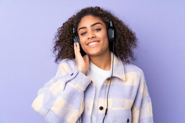 Молодая афро-американская женщина изолированная на фиолетовой слушая музыке