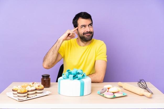 頭に指を置く狂気のジェスチャーを作る大きなケーキを持つテーブルの男