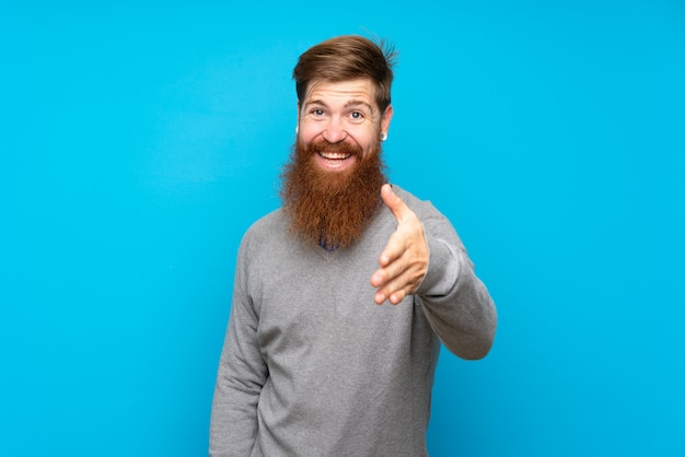 Рыжий мужчина с длинной бородой над изолированной синей рукопожатие для закрытия хорошей сделки