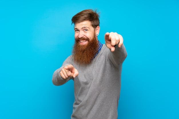 Рыжий мужчина с длинной бородой над изолированными синими пальцами указывает на вас во время улыбки