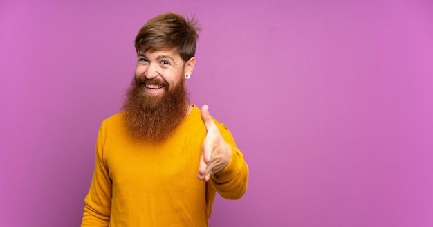 Рыжий мужчина с длинной бородой на изолированных фиолетовый рукопожатие для закрытия хорошей сделки