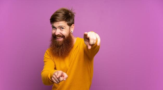 Рыжий мужчина с длинной бородой над изолированным фиолетовым указывает пальцем на вас во время улыбки