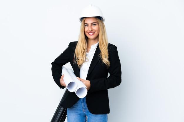 Молодая женщина архитектора с шлемом и держать светокопии над изолированным белым аплодируя