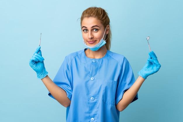 分離された青の上のツールを保持している若い女性歯科医