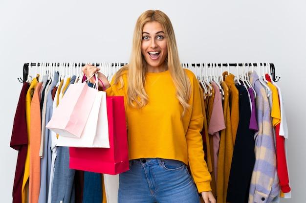衣料品店で驚きとショックを受けた表情で買い物袋を保持している若いウルグアイのブロンドの女性