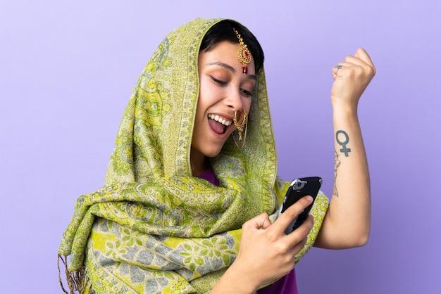 孤立した壁の上の若いインド人女性