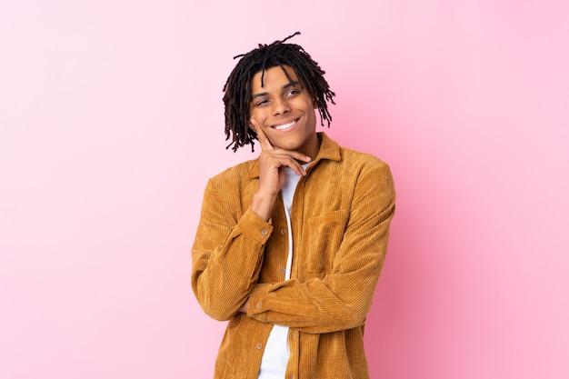 孤立したピンクの壁の上の若い男