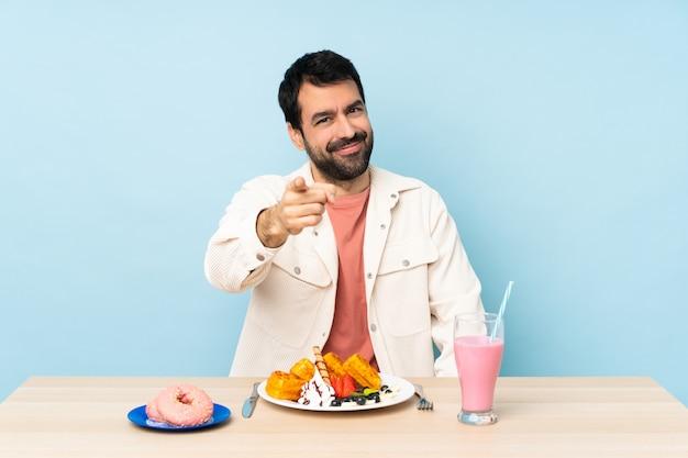 Мужчина за столом завтракает вафлями и молочный коктейль показывает пальцем на вас с уверенным выражением лица