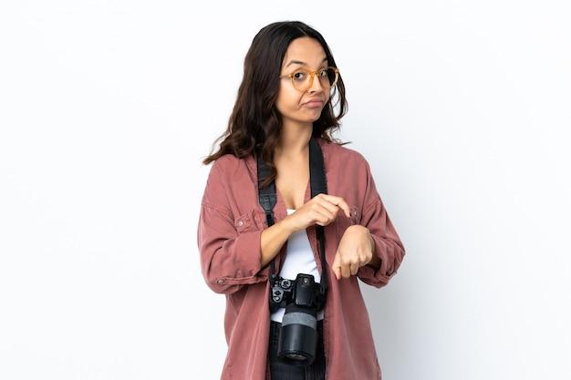 Молодой фотограф женщина над белой стеной, делая жест опоздания