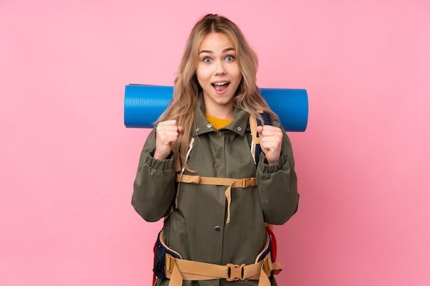 Русская девушка-альпинистка с большим рюкзаком на розовой стене празднует победу в победной позиции