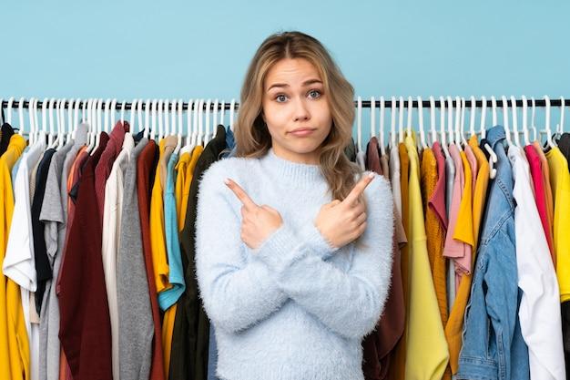 ロシアの女の子が青い壁に服を買う