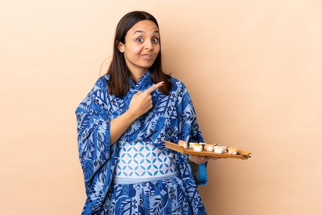 着物を着て壁に寿司をかざす女