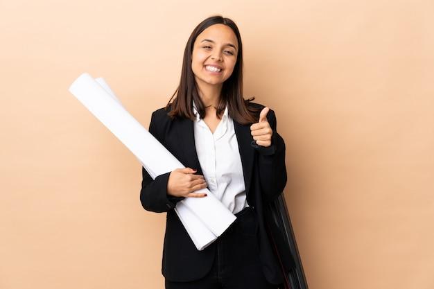 Молодой архитектор женщина, держащая чертежи на стене, держащей пустое пространство на ладони, чтобы вставить объявление и с большими пальцами руки вверх