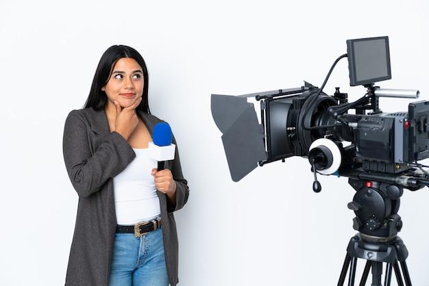 マイクを持っていると見上げながらアイデアを考えて白い壁にニュースを報告する女性記者