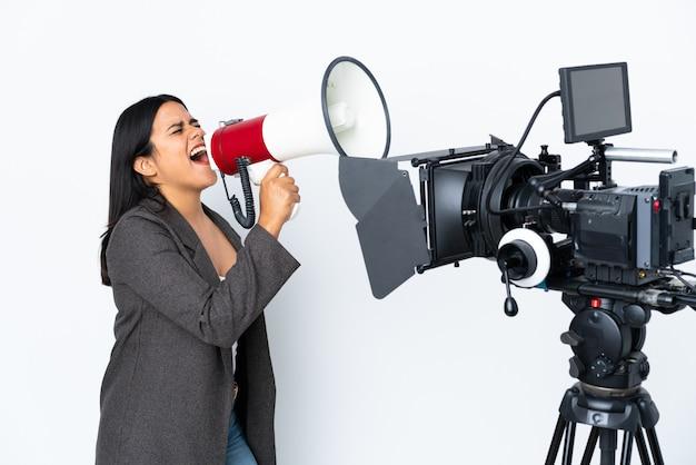 Репортер женщина, держащая микрофон и сообщения о новостях на белой стене, крича через мегафон