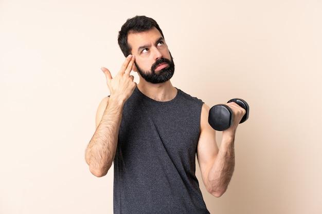 自殺ジェスチャーを作る問題で壁を越えて重量挙げを作るひげを持つ白人スポーツ男