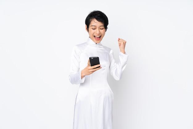 勝利の位置に電話で白い壁に伝統的なドレスを着て短い髪の若いベトナム人女性