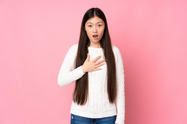壁を越えて若いアジアの女性は右を見ながら驚いてショックを受けた