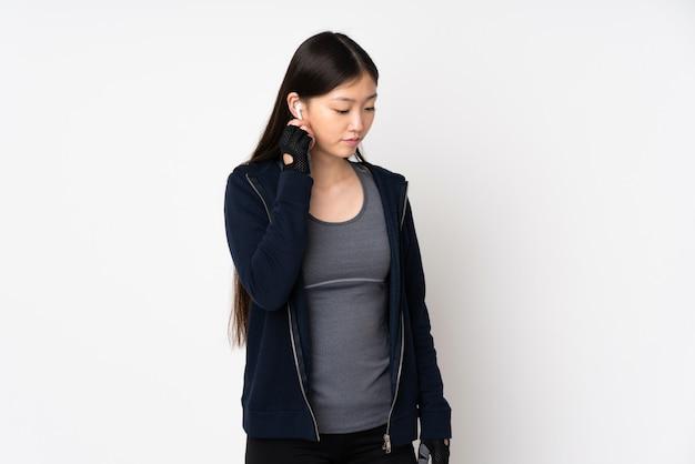Женщина молодого спорта азиатская на музыке белой стены слушая