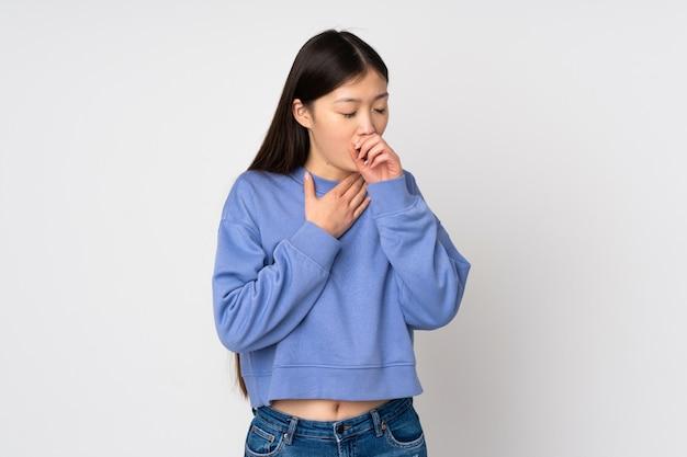 たくさん咳をする壁に若いアジアの女性