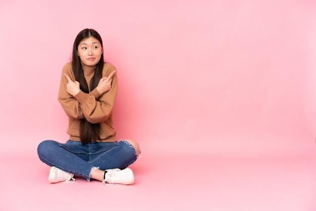 疑問を持つ側根を指しているピンクの壁の床に座っている若いアジア女性