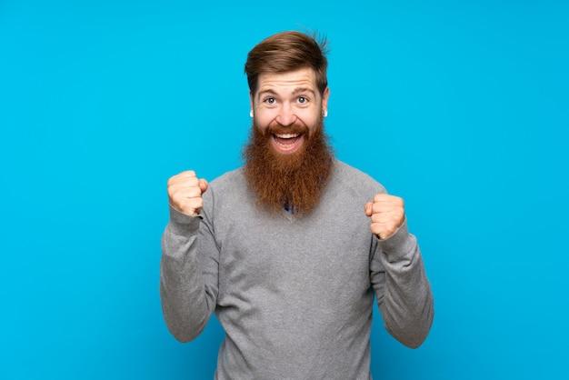 勝者の位置で勝利を祝っている青い壁の上の長いひげを持つ赤毛の男