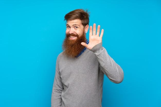 幸せな表情で手で敬礼青い壁に長いひげを持つ赤毛の男