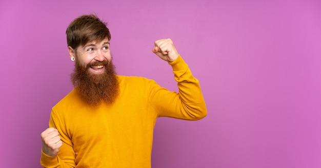 勝利を祝っている紫色の壁に長いひげを持つ赤毛の男